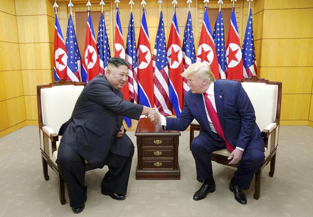 板門店の韓国側施設で握手する北朝鮮の金正恩朝鮮労働党委員長(左)とトランプ米大統領=30日(ロイター)