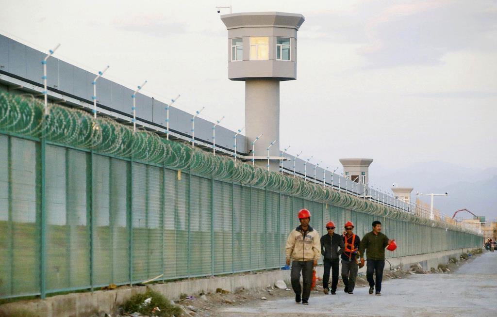 中国新疆ウイグル自治区の「職業教育訓練センター」のフェンス脇を歩く人々=2018年9月(ロイター)