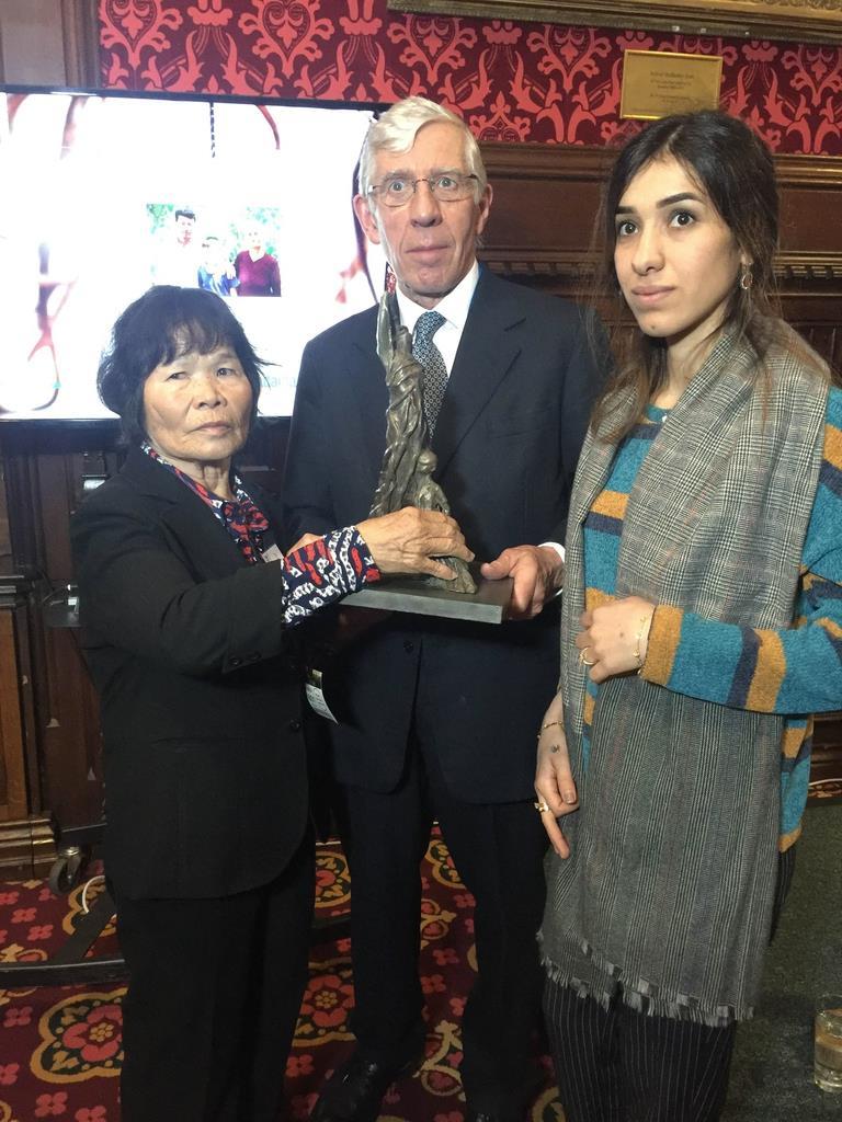 16日、英議会ストレンジャー・ダイニングルームで開かれた韓国のベトナム戦争性犯罪「ライダイハン」問題を追及する集会でライダイハン像を持つストロー元英外相(中央)と、ノーベル平和賞受賞者、ナディア・ムラド氏(右)=岡部伸撮影